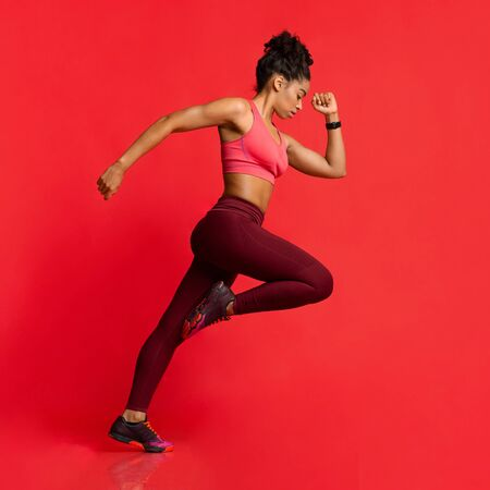 Black athletic girl in sportswear running over red background Banque d'images - 138299412