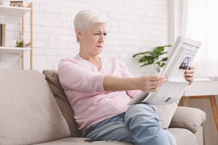 Bad sight problem. Senior lady squinting and holding newspaper far from eyes at home, free space Reklamní fotografie