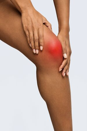 Cropped of african woman touching her knee, having joint pain