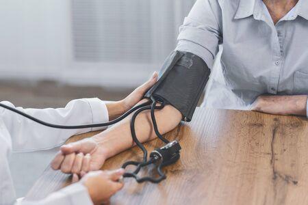 Community Outreach. Unrecognizable nurse measuring blood pressure of elderly man at home, copyspace, close up, copyspace