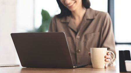 Coffee Time. Unrecognizable smiling girl using laptop and holding mug with hot drink beverage, panorama Banque d'images - 138297686