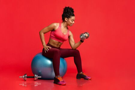 Black fitness model pumping iron, sitting on fitness ball over red studio background, free space