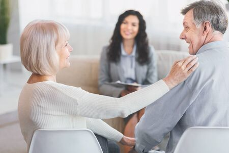 Healthy Relationship. Happy elderly couple reconciling at therapy session, female psychologist in the background