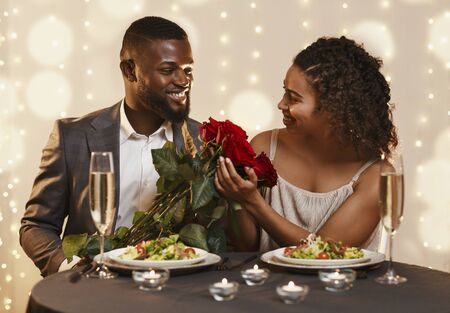 Handsome black guy giving beautiful flowers to his girlfriend, having valentine date at restaurant