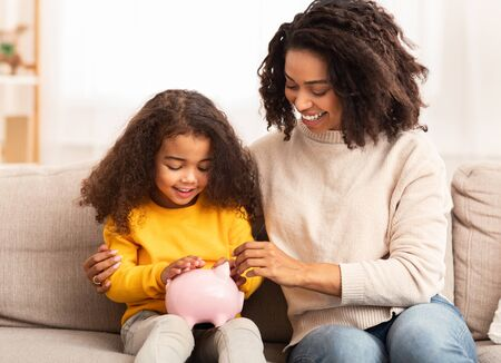 Family Savings. Cheerful Afro Mother Teaching Little Daughter How To Save Money Holding Piggybank Sitting On Sofa At Home Foto de archivo - 138299937