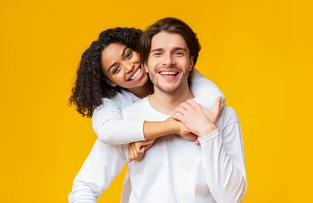 Portrait of young interracial couple in love cuddling and posing over yellow background, smiling and looking at camera, free space Foto de archivo - 138299989