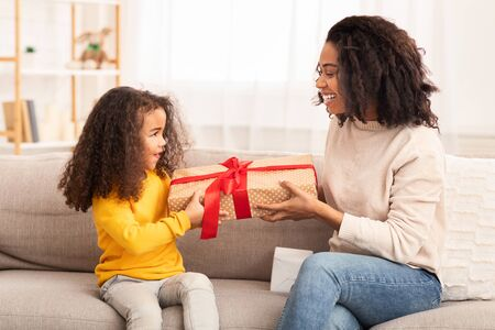 African American Mom Giving Gift To Little Daughter Congratulating On Birthday Sitting On Couch At Home. Family Holiday Concept Foto de archivo - 138300085