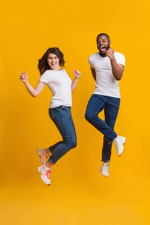 Great discount. Joyful interracial couple jumping in air and shouting with excitement over yellow background in studio Foto de archivo - 138300138