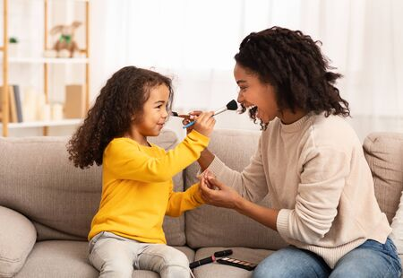 Mother And Daughter Relationship. Loving Mom And Little Kid Having Fun Making Makeup Together At Home. Selective Focus Stok Fotoğraf - 138300244