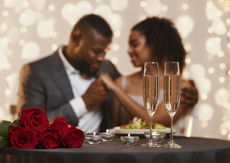 Two glasses of champagne and bunch of red roses over black couple in love, celebrating Valentines Day at restaurant Foto de archivo - 138300451