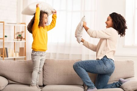 Family Fun. Happy Afro Mother And Daughter Playing Having Pillow Fight Together At Home. Selective Focus Foto de archivo - 138299699