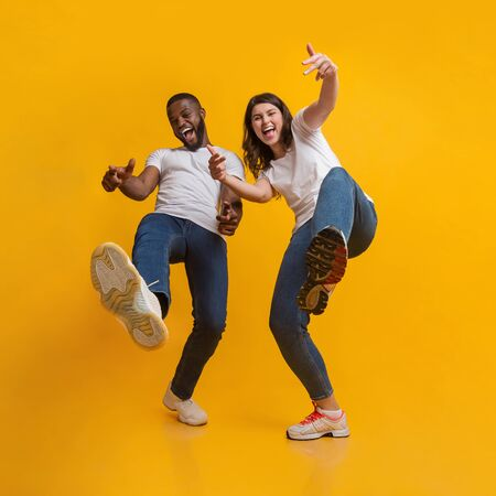 Yo. Positive interracial couple fooling together, having fun and laughing at camera over yellow studio background, low angle view Foto de archivo - 138300520