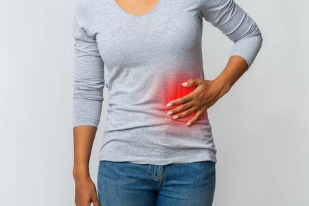 Cropped of black woman in pain holding her stomach on the left side, grey background, gastrointestinal tract diseases Reklamní fotografie