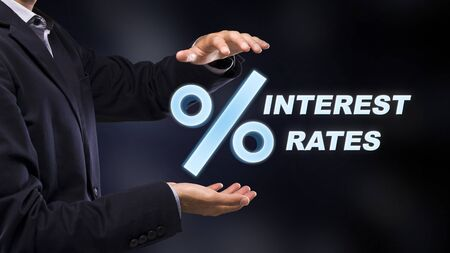 Unrecognizable businessman holding percentage mark with interest rates inscription in hands, standing over dark background, side view panorama