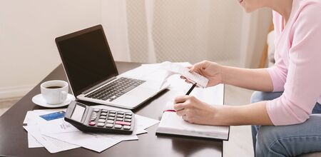 Counting purchases. Senior lady writing calculation in notebook with bills, panorama Stock Photo