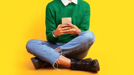 Teenage Pastime. Unrecognizable black girl sitting on the floor using smartphone over yellow studio wall, copyspace Stock Photo