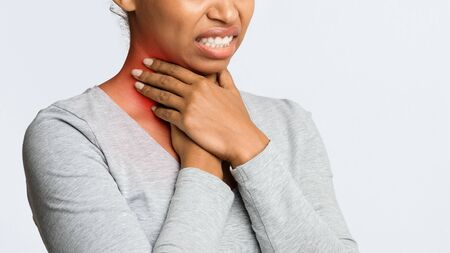 Angina, tonsillitis. Cropped of black woman holding her inflamed throat, panorama with free psace