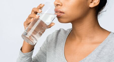 Close up of black young woman drinking water over grey background, hydration concept