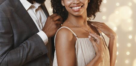Cropped of african american man giving woman beautiful golden chain, celebrating anniversary together, panorama