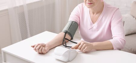 Hypertension. Mature woman checking her blood pressure with tonometer at home, panorama with free space Banco de Imagens