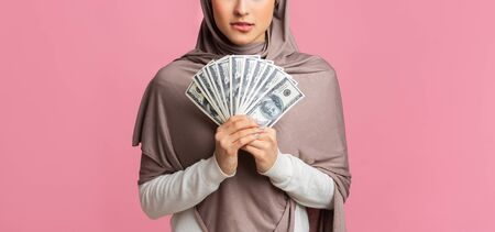 Money In Islam Concept. Doubtful arabic woman holding fan of dollar cash in hands, thinking about haram investment over pink background, panorama