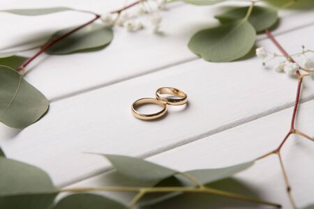 Pair of gold wedding rings on wooden background with leaves. Two-tone wedding rings. Romantic fashion jewelry advertising
