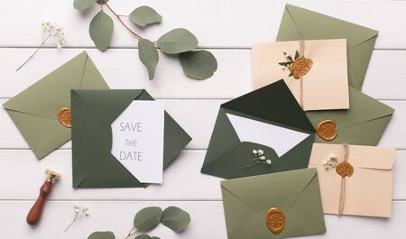 Wedding planning. Stylish dark green envelopes with accessories on white background