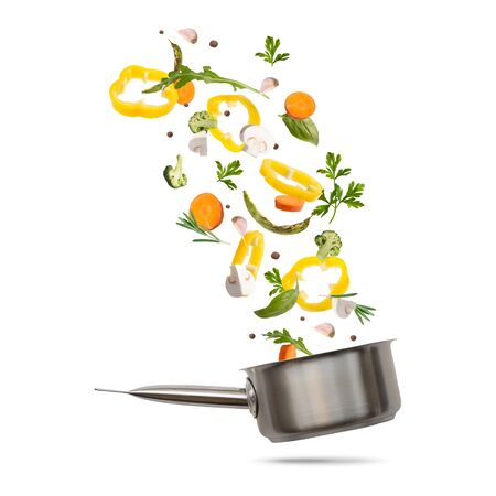 Healthy vegetarian eating and cooking with various flying chopped vegetables ingredients, cooking pot on white background