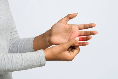 Young black woman suffering from pain in hand and massaging her painful finger, grey background