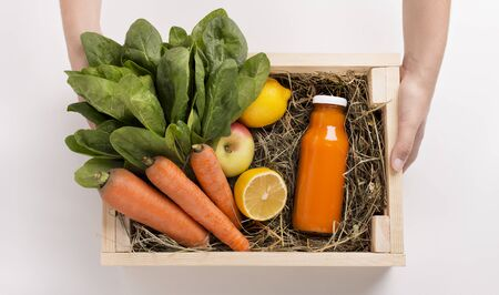 Detox cleanse drink concept. Fresh fruits and vegetables ingredients in wooden box with healthy cocktail on white background Banco de Imagens