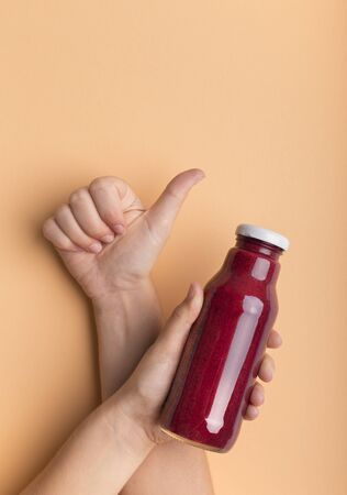 Supreme drink for recharging energy balance. Woman showing thumb up and holding bottle with red beet smoothie on orange background, copy space