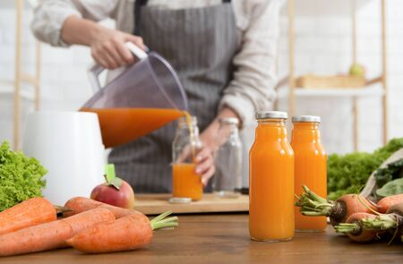 Making orange detox take-away smoothie. Woman in linen apron pouring smoothie drink from blender to bottle surrounded with vegetables and greens