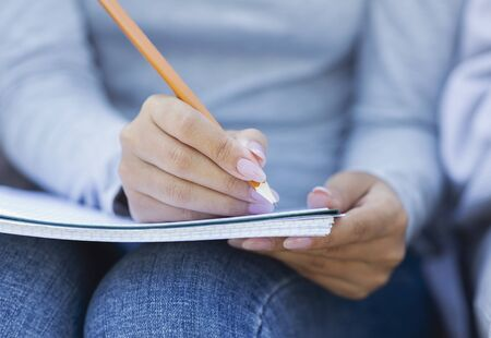Cropped of student girl taking notes, studying with friends, using notepad and pencil Banco de Imagens