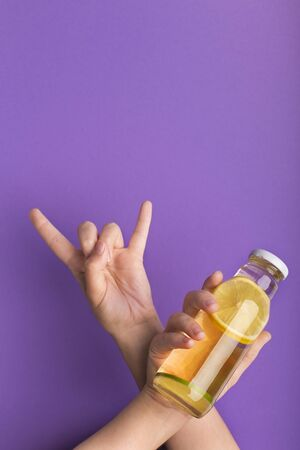 Woman showing horn sign and holding bottle with delicious lemon detox water on purple background, copy space