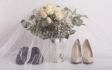 Braut- und Bräutigamzubehör. Hochzeitsschuhe unter Schleier mit Brautstrauß, weißer Hintergrund Standard-Bild
