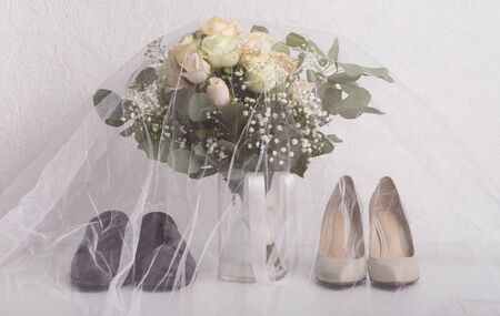 Bride and groom accessories. Wedding shoes under veil with bridal bouquet, white background