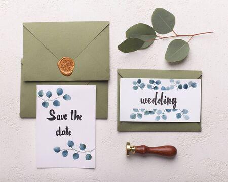 Hochzeitseinladungskarten Papiere, die auf Tischdekoration mit Blättern liegen, speichern Sie den Datumstext