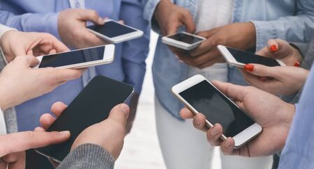 Modern communication and gadget addiction concept. Closeup of diverse people standing in circle holding smartphones, panorama