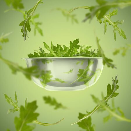 Healthy greens. Flying rucola from plate over green background Banco de Imagens