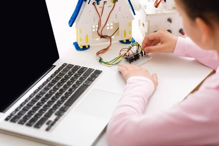Girl constructing robot and programming it on laptop computer, studying at stem class