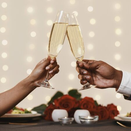 Valentine dinner. Cropped of african man and woman toasting with champagne, having dinner in restaurant