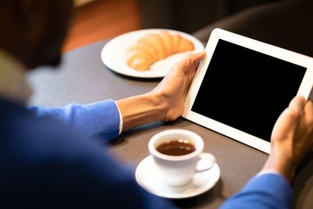 Breakfast At Cafe. Unrecognizable afro manager holding tablet with empty blank screen at coffee break, mock up, close up