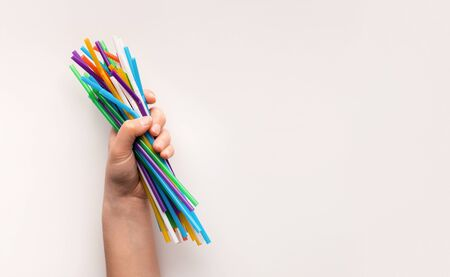 Plastic ocean pollution, environmental crisis. Hand holding heap of used plastic straws on white background, copy space