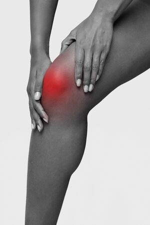 Monochrome cropped photo of african woman massaging her sore knee, legs trauma concept