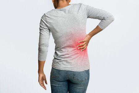 Cálculos renales. Mujer afro sosteniendo su mano detrás de la espalda, dolor en el riñón, zona inflamada resaltada en rojo, vista posterior