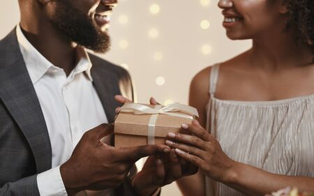 Happy Valentine Day honey. Close up of black romantic guy giving present to his girlfriend Banco de Imagens