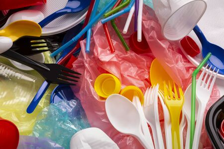 Choose life without plastic. Colored single-use plastic and other plastic items on background.