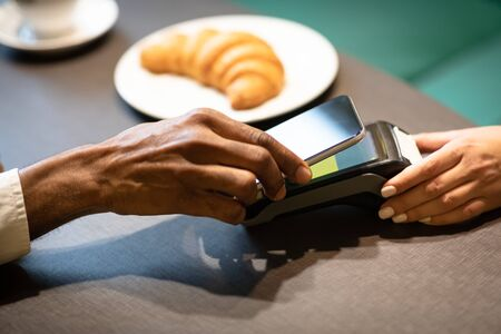 Online Bill Payment Concept. Black man holding smartphone close to electronic payment machine while paying in cafe