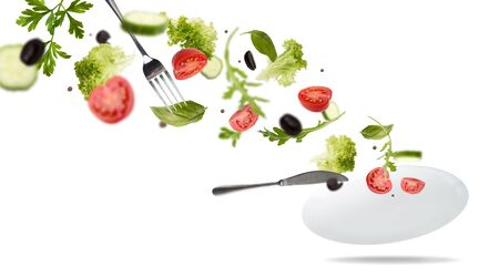 White plate with salad in flight: tomato, lattice, olives and greens on white background, panorama