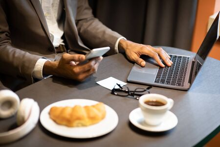 Busy Man. Close up of black mans hands using smartphone in cafe interior, typing on laptop keyboard, having breakfast